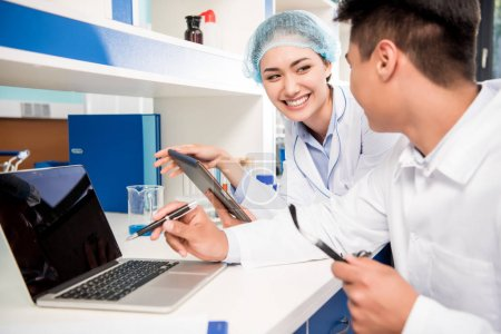 Photo for Smiling scientists working in laboratory with laptop and digital tablet - Royalty Free Image