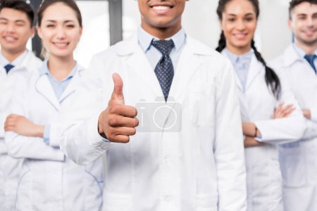 Photo for Team of young professional doctors standing together in laboratory while their leader is showing thumb up - Royalty Free Image