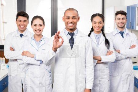 Photo pour Équipe de sourire professionnels médecins debout ensemble, alors que leur chef est montrer signe OK - image libre de droit