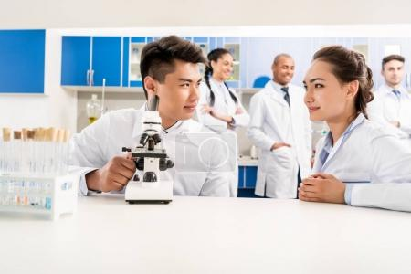Photo for Two doctors working with microscope in laboratory while their colleagues are standing behind - Royalty Free Image