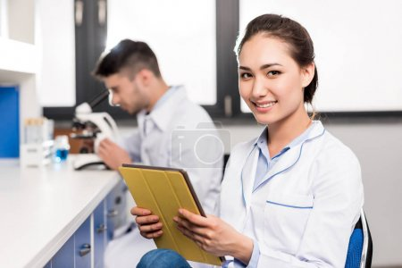 smiling doctor with digital tablet
