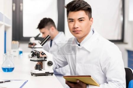 Young scientist with microscope