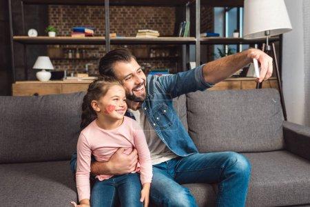 Photo pour Père et fille prendre selfie tandis que assis sur le canapé à la maison - image libre de droit
