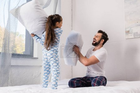 Photo for Happy father and daughter playing pillow fight in bed at morning - Royalty Free Image