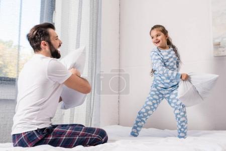 Photo pour Heureux père et fille se battant avec des oreillers dans le lit le matin - image libre de droit
