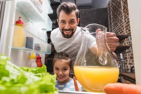 father and daughter taking juice from fridge