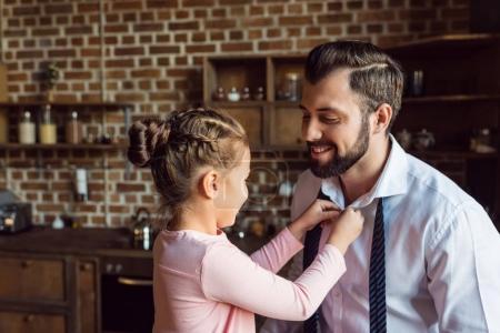 Photo pour Petite fille boutonnage chemise pour père sur la cuisine - image libre de droit