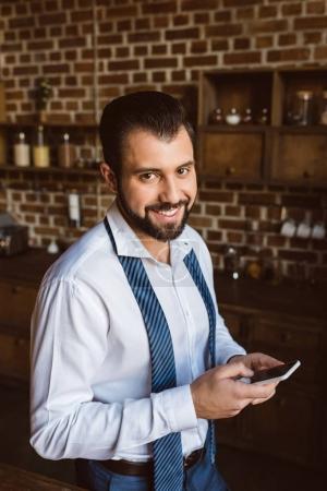 Photo pour Homme d'affaires à l'aide de smartphone sur la cuisine et en regardant la caméra - image libre de droit
