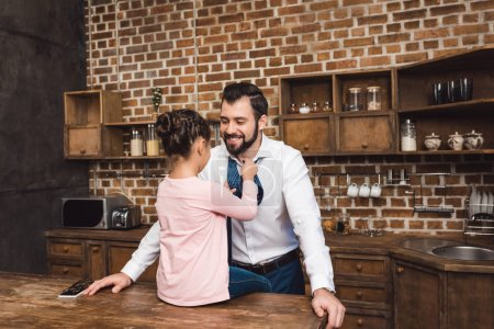 daughter tying up necktie for father