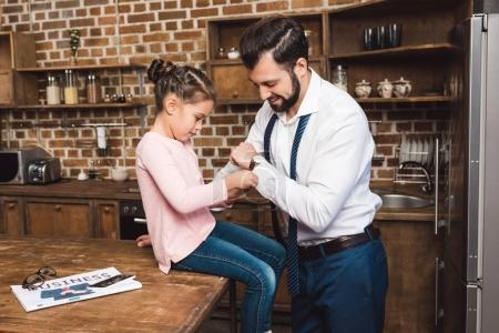 daughter fixing cufflinks for father