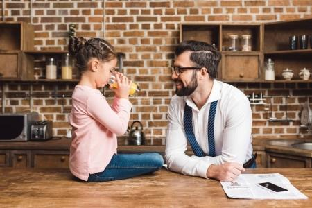 Father looking at daughter drinking juice