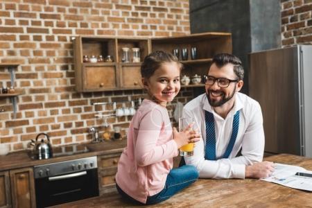Photo pour Père regardant fille avec du jus dans les mains alors qu'elle est assise sur la table - image libre de droit