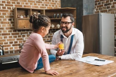 Photo pour Heureux père donnant verre de jus fille alors qu'elle est assise sur la table - image libre de droit