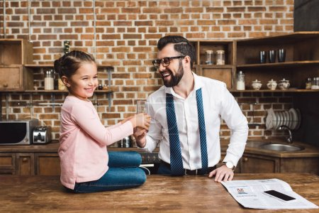 Father giving glass of juice daughter