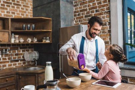 Photo pour Heureux père faire des céréales petit déjeuner pour fille pendant qu'ils se préparent pour le travail et l'école - image libre de droit