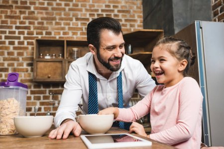 Photo pour Beau père heureux et petite fille petit déjeuner à la cuisine - image libre de droit