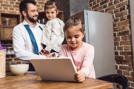 girl using tablet on kitchen