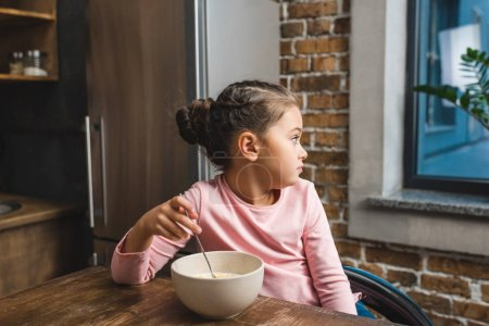 child with bowl of breakfast