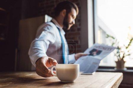 Photo pour Homme d'affaires concentré, lisant le journal dans la cuisine le matin tout en ayant la tasse de café - image libre de droit