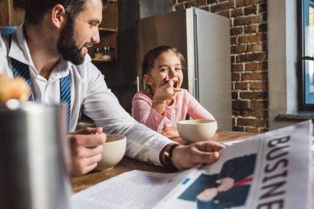 Photo pour Heureux père et fille manger le petit déjeuner ensemble pendant qu'ils se préparent pour le travail et l'école - image libre de droit