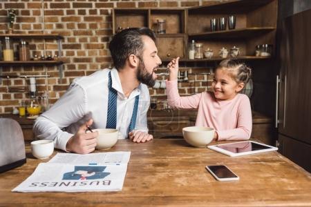 Photo pour Fille nourrir père avec des céréales sur la cuisine le matin pendant qu'ils se préparent pour le travail et l'école - image libre de droit