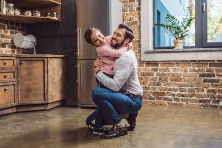 Photo pour Jeune père heureux et petite fille embrassant sur la cuisine - image libre de droit