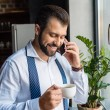 Smiling businessman talking by phone on kitchen wi...