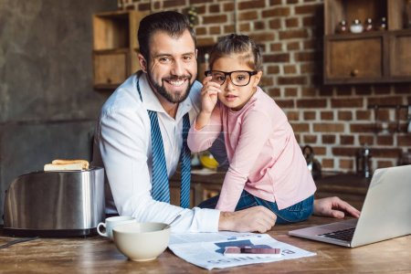 father and daughter sitting on kitchen