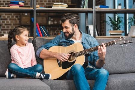 Photo for Father playing guitar for daughter at home while sitting on couch - Royalty Free Image