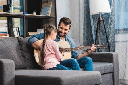 Photo pour Heureux jeune père apprendre fille à jouer de la guitare - image libre de droit