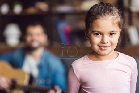 Photo pour Petit enfant adorable regardant la caméra avec un père flou sur fond - image libre de droit