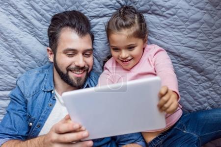 Photo pour Vue de dessus du père et de la petite fille heureuse en utilisant la tablette au lit - image libre de droit