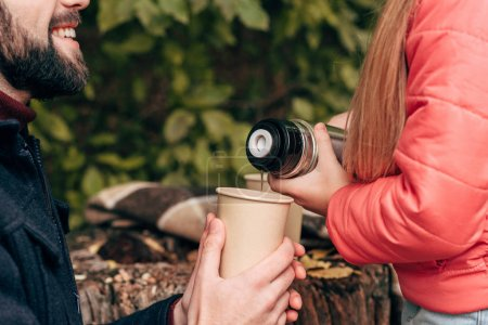 child pouring tea from thermos