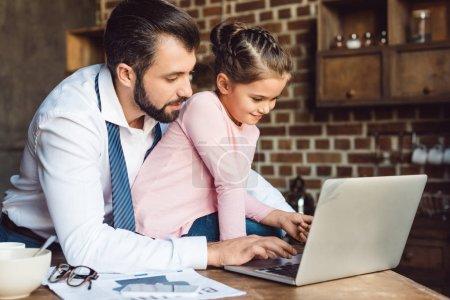 Photo pour Beau père et fille en utilisant ordinateur portable ensemble sur la cuisine - image libre de droit