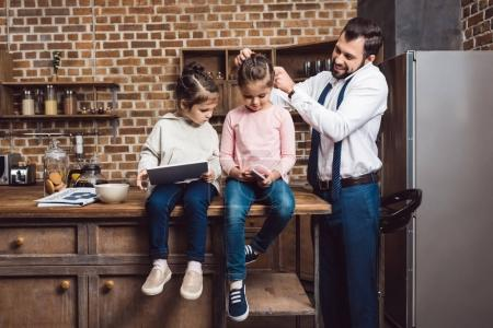Photo for Father and daughters preparing for school and work in morning on kitchen with digital devices - Royalty Free Image