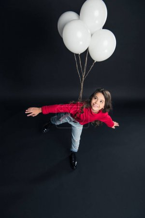 kid imitating flying with balloons