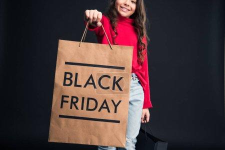 Photo pour Image recadrée de Kid montrant sac à provisions avec signe Black Friday isolé sur noir - image libre de droit