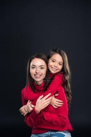 Photo for Daughter hugging mother and looking at camera isolated on black - Royalty Free Image