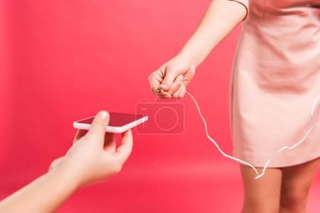 plugging earphones into smartphone