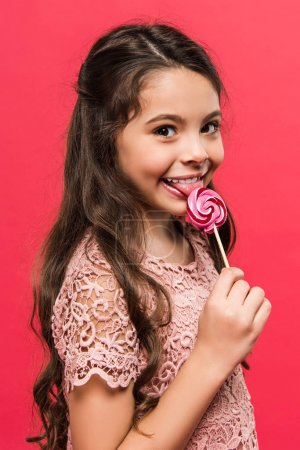 child licking colored lollipop