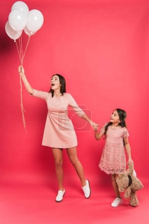 mother and daughter looking at helium balloons