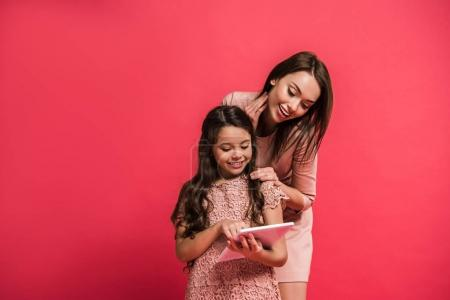 Photo for Smiling mother and daughter looking at tablet isolated on red - Royalty Free Image
