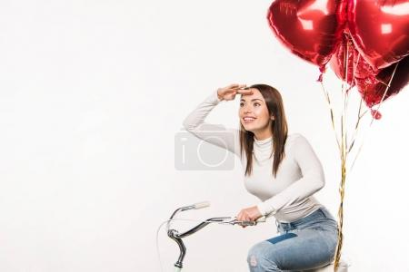 woman sitting on bike with balloons