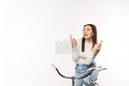 Photo pour Femme souriante assise sur le vélo et pointant sur quelque chose d'isolé sur blanc - image libre de droit