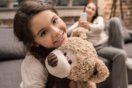 Photo for Selective focus of smiling daughter with teddy bear and mother using smartphone at home - Royalty Free Image