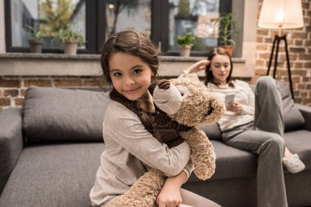 daughter with teddy bear at home