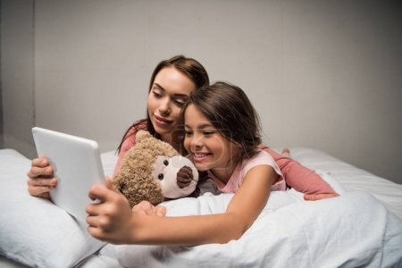 Photo for Portrait of mother and daughter using tablet together while lying on bed at home - Royalty Free Image