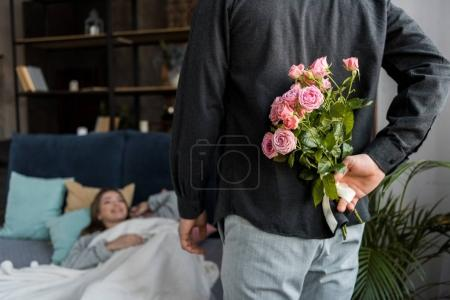 boyfriend hiding bouquet of roses from girlfriend on international womens day
