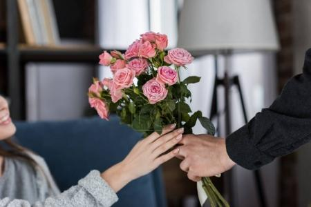 cropped image of boyfriend presenting bouquet of roses to girlfriend on international womens day