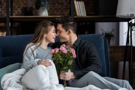 boyfriend presenting bouquet of roses to happy girlfriend on international womens day